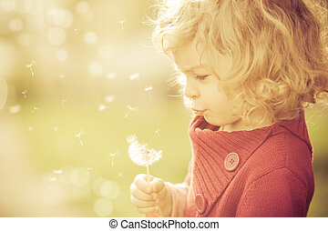 Sunny day - Beautiful child blowing away dandelion flower in...