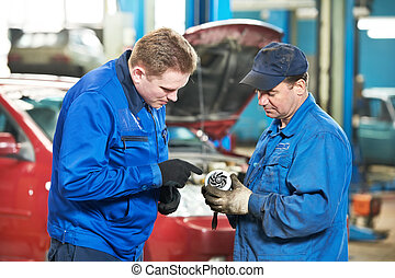 two car mechanic diagnosing auto engine problem - two...
