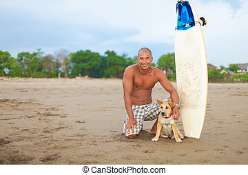young man and dog - young man with surfboard and dog on...