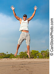 young man jumping in the air on the beach