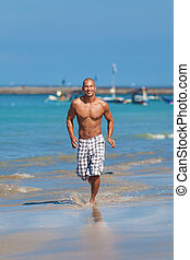 young man running on beach - young muscular man running on...
