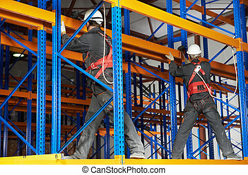 two warehouse workers installing rack arrangement - team of...
