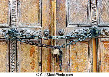 Locked wooden door - An old wooden door locked by a chain...
