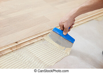 gluing parquet floor work - Close-up hand of handyman...