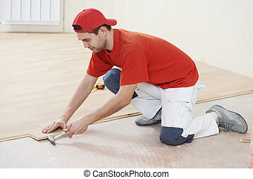 carpenter worker joining parket floor - carpenter worker...