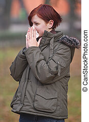 Flu season - Girl blowing her nose outdoors in late autumn.