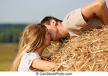 Young couple kissing on a haystack on harvested field