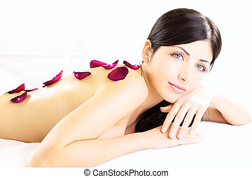 Angelic portrait of beauty with flower on naked back in white spa
