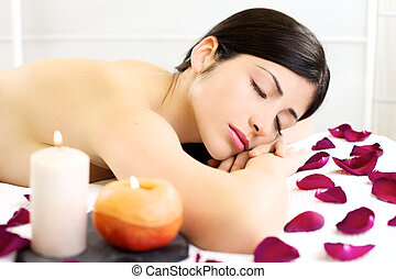Beautiful woman relaxing sleeping naked during massage in spa