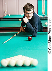 Snooker billiard player - Young player man with cue at the...