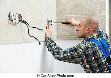 Electrician installing wall outlets - Young electrician at...