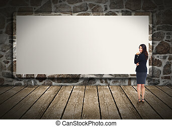Business woman near billboard - Business woman standing near...