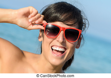 Playful happy woman with red glasses on the beach - Playful...