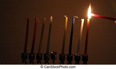 Ignition Chanukah candles in the brass candleholder