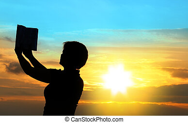 female praying with bible against summer sunset, person isnt...