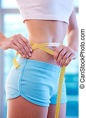 Weight control - Close-up of slender woman measuring her...