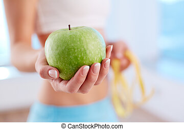 Healthy nutrition - Close-up of female hand holding green...