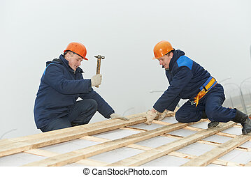 roofing workers hammer roof boarding - two roofers nailing...