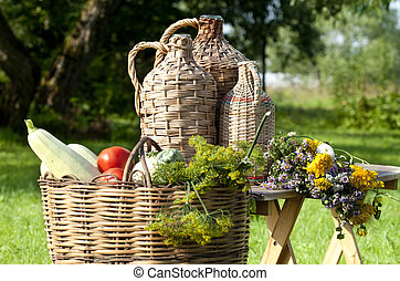 Rural still life with demijohns and basket of vegetables