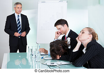 Bored businesswoman sleeping in a meeting as her colleague...