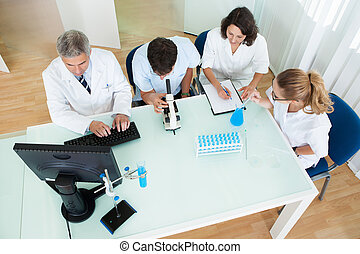 Laboratory technicians at work - Overhead view of four...
