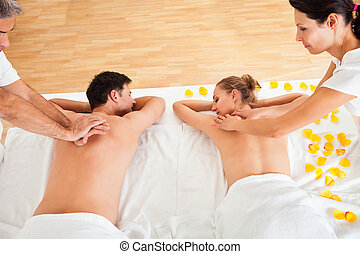 Relaxing massage for two - Young couple relaxing and...