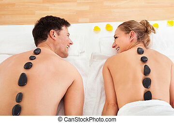 Couple enjoying a hot stone massage in a spa where heated...