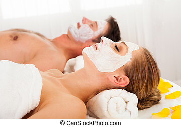 Man and woman in face masks lying back on clean white towels...