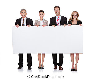 Businesspeople holding a blank banner - Four diverse...