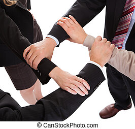 Businesspeople linking hands - teamwork - Cropped overhead...