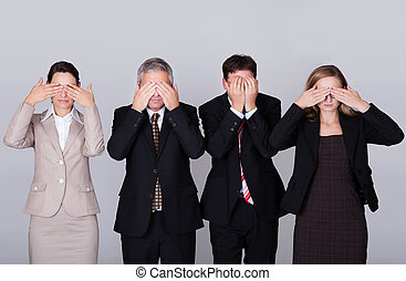 Four businesspeople holding their eyes shut - Four diverse...