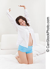 Young woman stretching after waking up