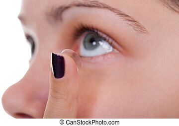 Woman inserting a contact lens - Cropped view of a woman...