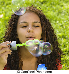 Girl blows bubbles - A teenage girl blows bubbles with a...