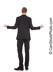 full body back view of a business man welcoming you on white...