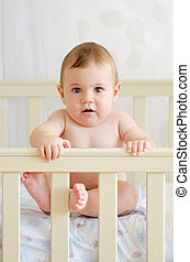 baby sitting in a crib - naked child sitting in a crib and...