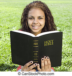 Teen with bible in park - A teenage girl hangs out in a park...