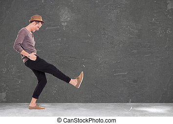 young man kicking and smiling - relaxed casual young man...