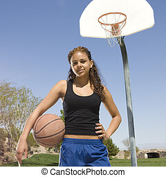Teen girl with basketball hangs out at the park