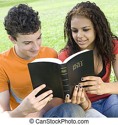 Two teens share bible - Two teens share a bible in a park