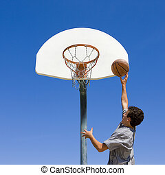 Teen jumps and shoots basketball - A teen boy jumps and...