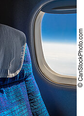 Seats and window in airplane - View of the blue sky from the...