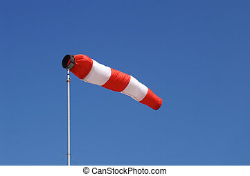 Windsock - Red and white windsock blows against a blue sky.