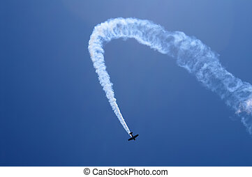 Loop - The plane in the dark blue sky does a loop, leaving a...
