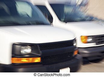 Two blurred vans - Two blurred white cargo vans