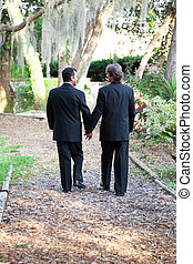 Gay Wedding Couple Walking on Garden Path - Two gay male...