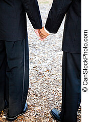 Gay Grooms Holding Hands - Closeup view of interracial gay...