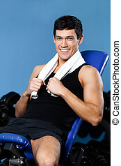 Athletic man rests in training gym - Athletic man rests...