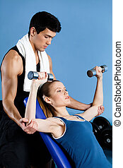 Coach helps woman to exercise with weights - Coach helps...