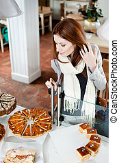 Girl in scarf looking at the bakery window
